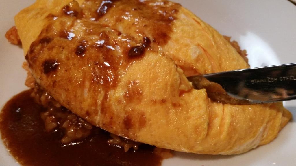 池袋『ウチョウテン(UCHOUTEN)』の、オムライスの卵にナイフを入れている写真