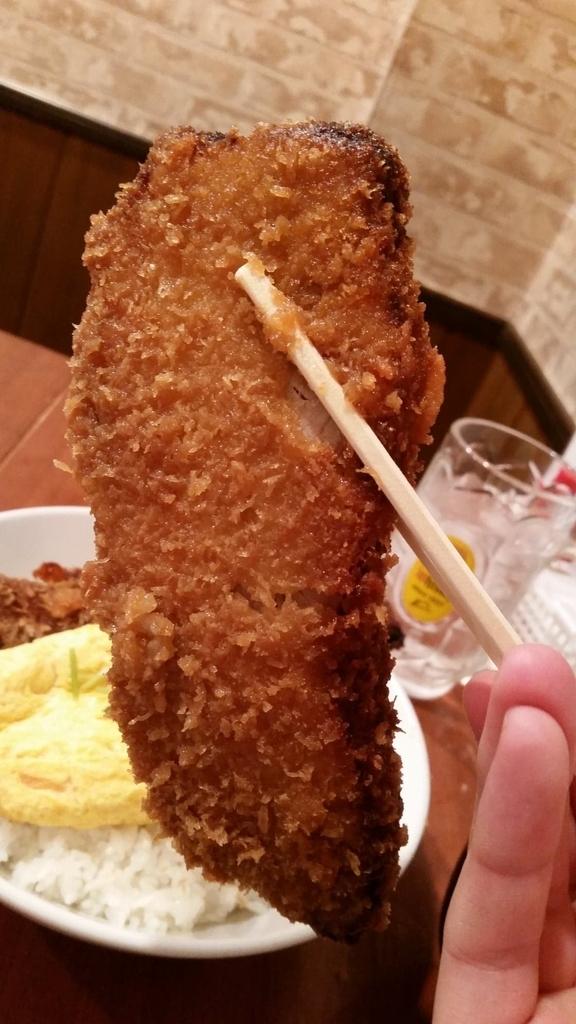 秋葉原『炉端バルさま田』の、とろとろ玉子の角煮かつ丼ダブル大盛りのカツを箸で持ち上げている写真