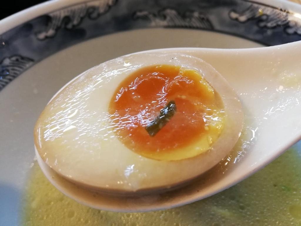 レンゲですくった特選塩ラーメンの半熟卵