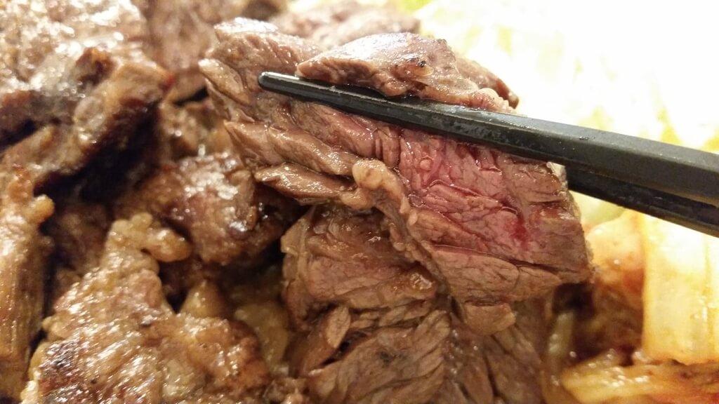 箸で掴んだ、丼やまののハラミ丼肉トリプルご飯大盛りのハラミ肉