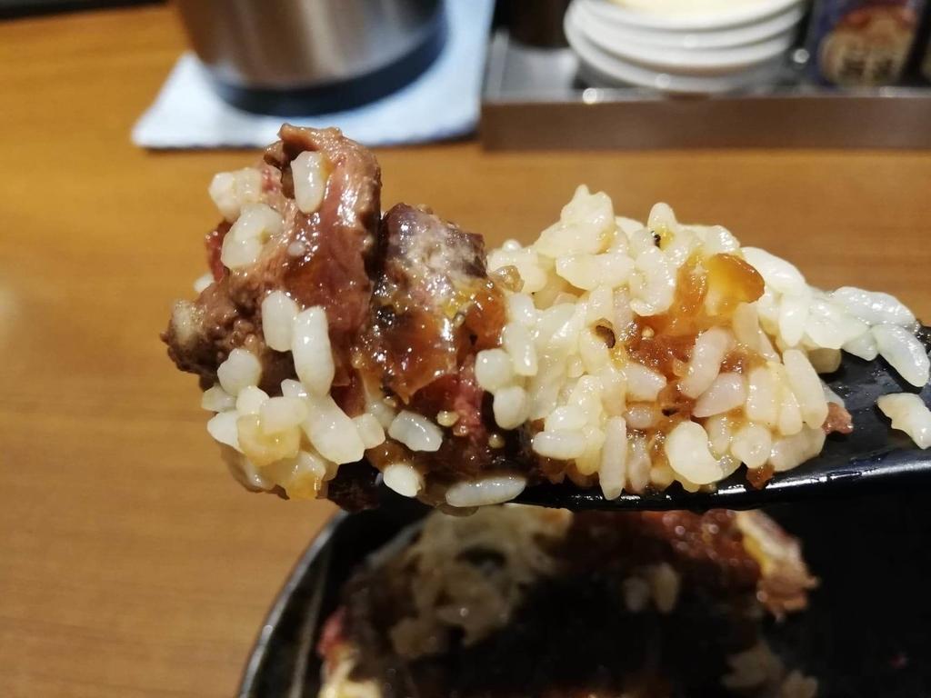 箸で掴んだ、秋葉原『1ポンドのステーキハンバーグ タケル』のタレのかかった旨馬丼