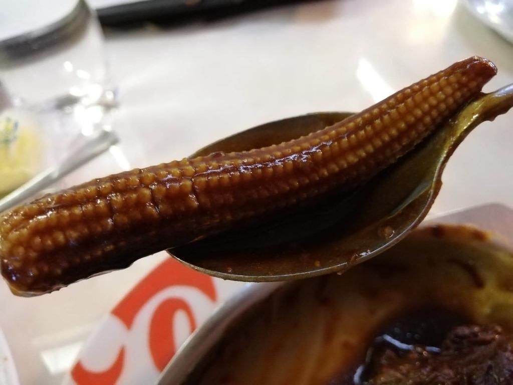 浅草『洋食屋ヨシカミ』のビーフシチューの中にあるミニコーンを、スプーンで持ち上げた写真