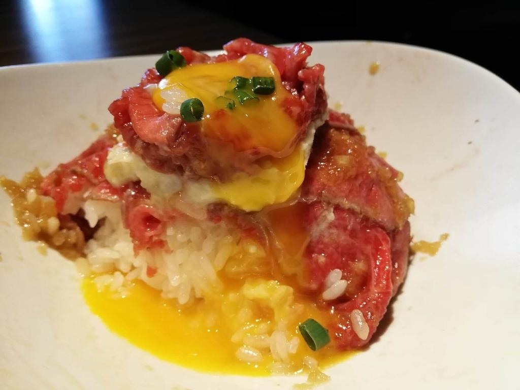 新宿『焼肉ブルズ』の特選和牛のローストビーフ丼に黄身がかかっている写真