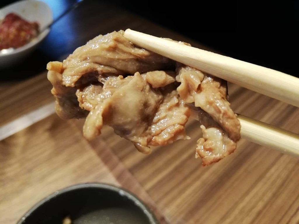 新宿『焼肉ブルズ』の小鉢の肉を箸で掴んでいる写真