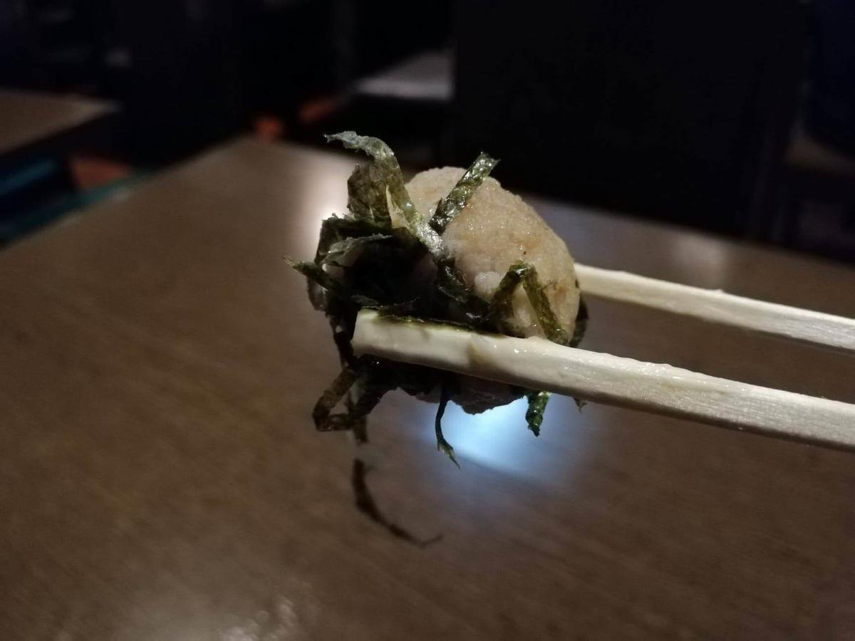 六本木『居酒屋のんでこ』のセクシーチャーハンのつくねを、箸で掴んでいる写真