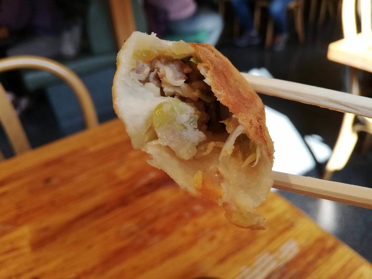 亀有『ホワイト餃子』の食べかけの焼き餃子を、箸で掴んでいる写真