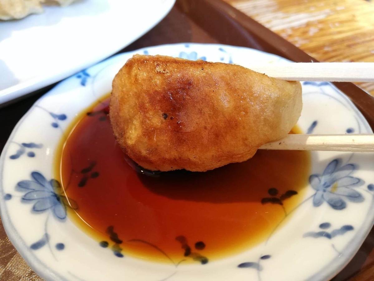亀有『ホワイト餃子』の焼き餃子を、醤油タレにつけている写真