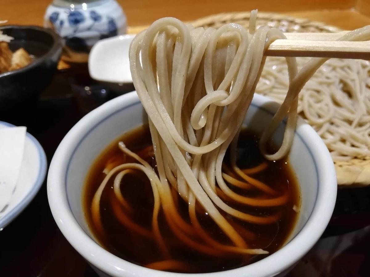 稲田堤『石づか』の蕎麦をつゆに浸けている写真