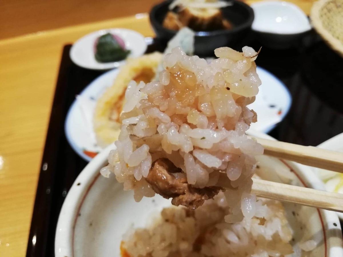 稲田堤『石づか』の炊き込みご飯を箸で掴んでいる写真