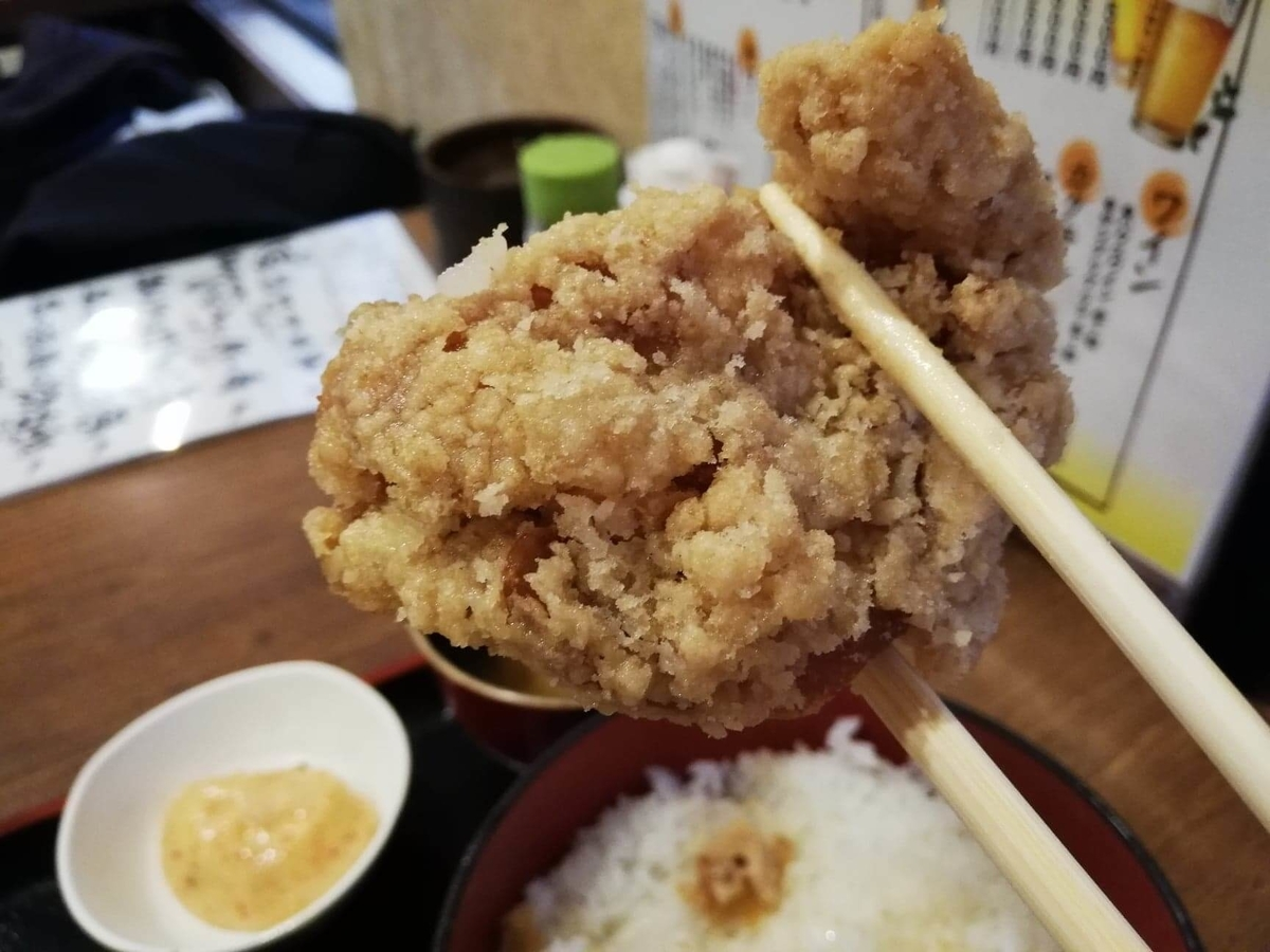 立川『ひなたかなた』のデカ盛り唐揚げ丼の唐揚げを、箸で掴んでいる写真