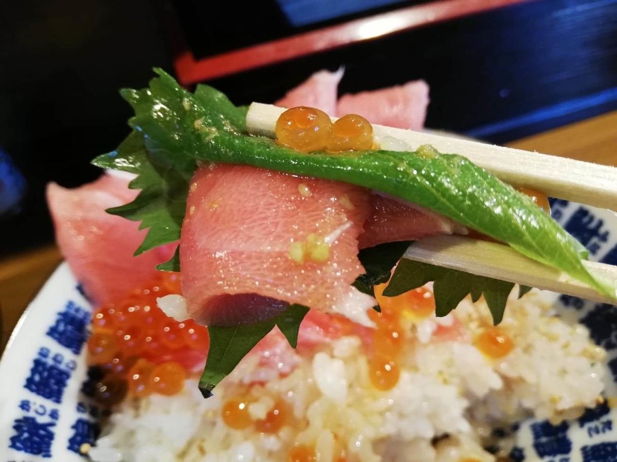 立川『モンロー』の天然本まぐろ中とろマシマシいくらマシマシ海鮮丼の、シソとまぐろを一緒に持ち上げている写真