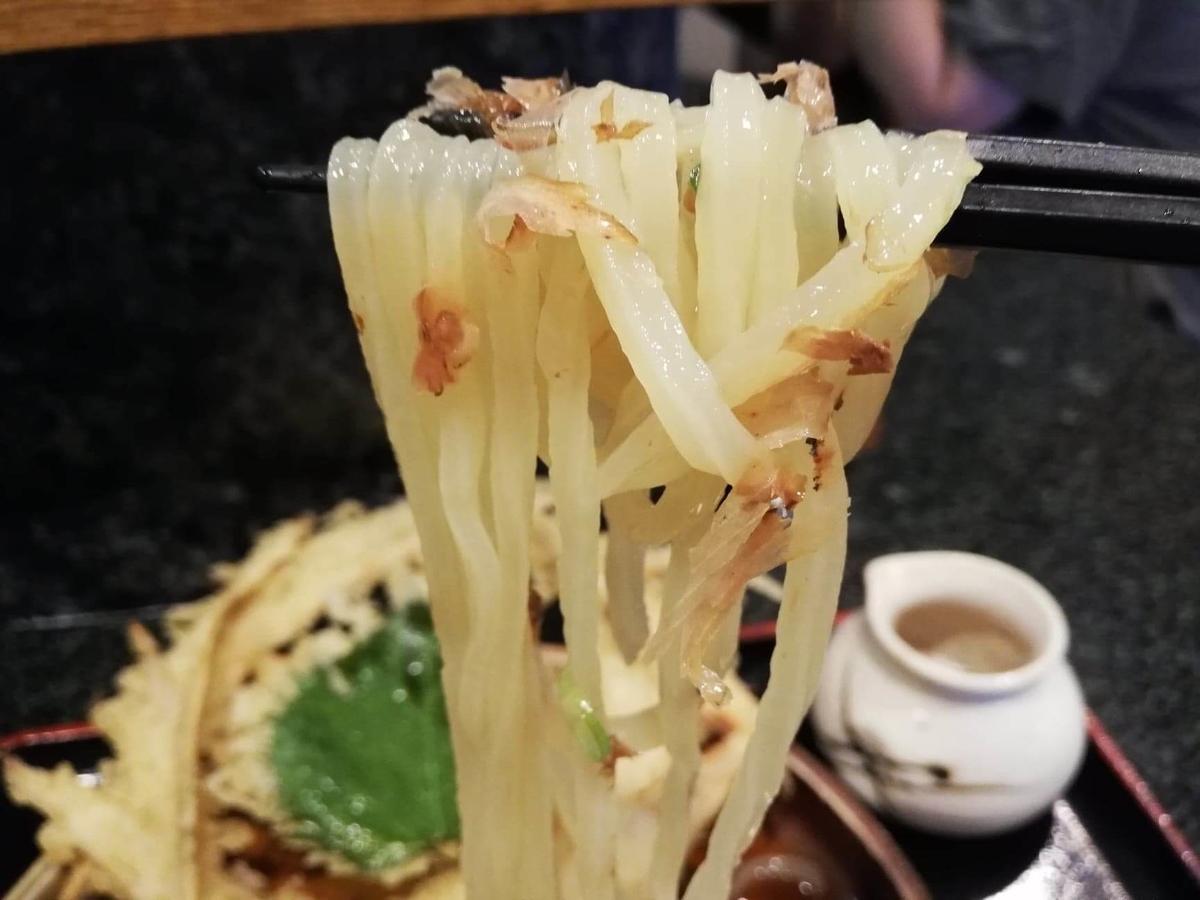 高田馬場『大地のうどん』のごぼうおろしぶっかけの麺を箸で掴んでいる写真