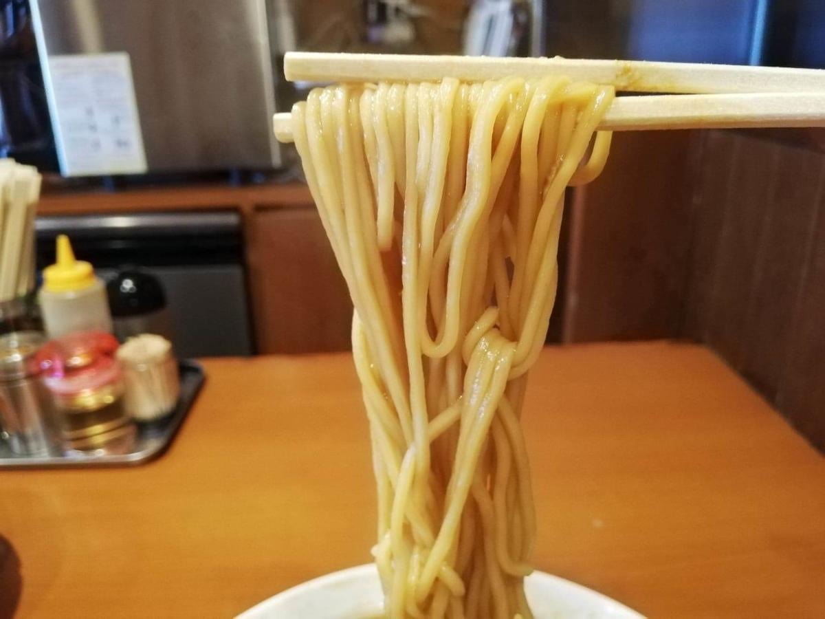 『末廣ラーメン本舗』高田馬場分店のチャーシュー麺の麺を、箸で掴んでいる写真