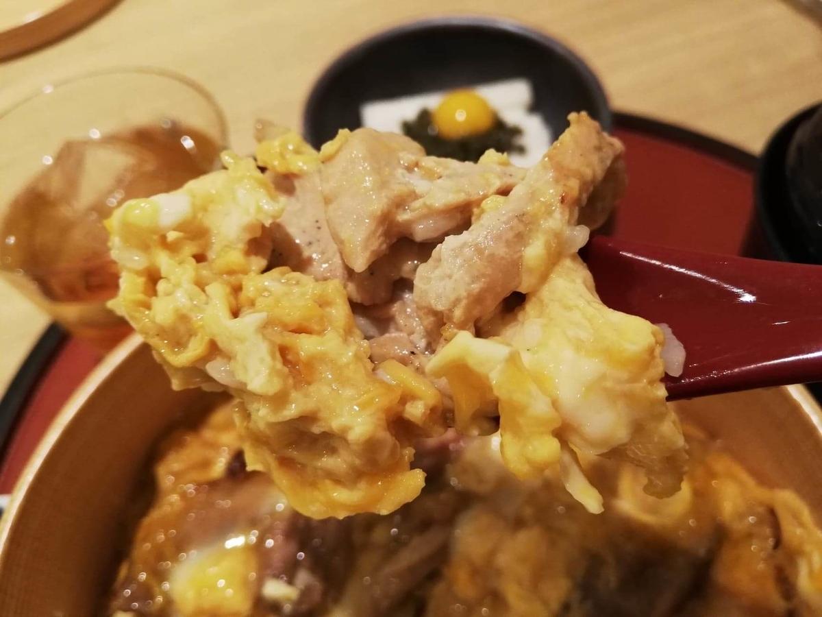 秋田駅『秋田比内地鶏や』の、比内地鶏の究極親子丼の地鶏をスプーンですくっている写真