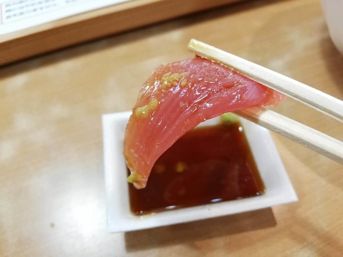 秋田市民市場のマグロを箸で掴んでいる写真