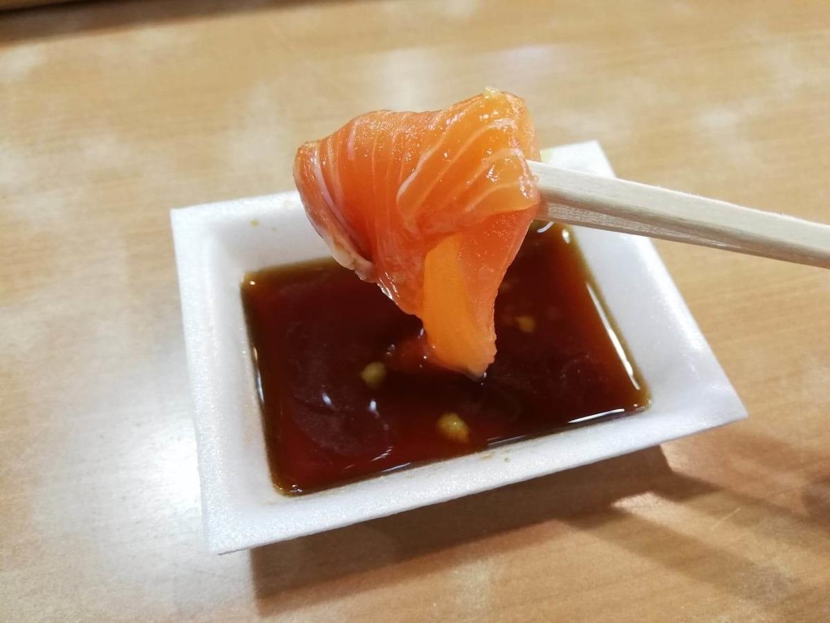 秋田市民市場のサーモンを箸で掴んでいる写真