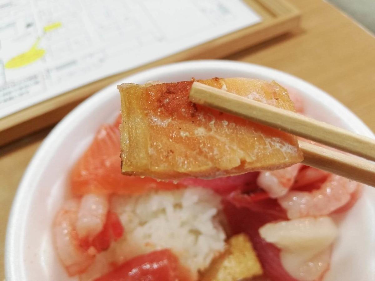 秋田市民市場のスモークはらすを箸で掴んでいる写真
