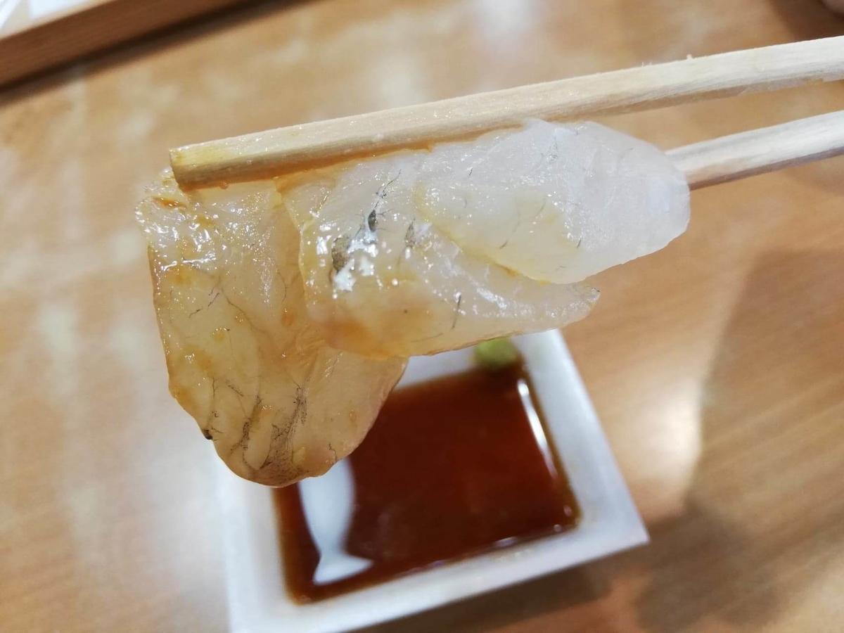 秋田市民市場のヒラメを箸で掴んでいる写真