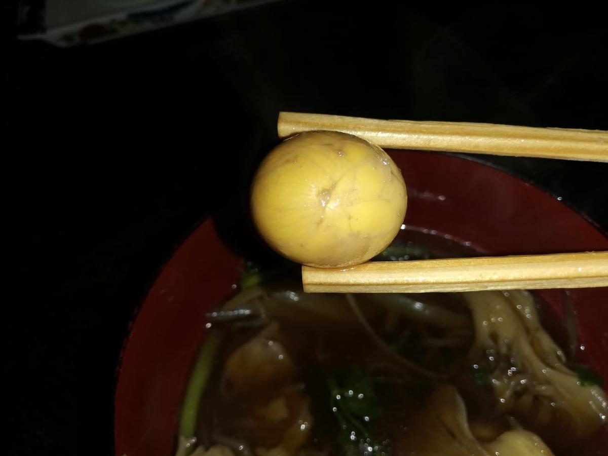 『秋田きりたんぽ屋』のきりたんぽ鍋の中のキンカンを、箸で掴んでいる写真