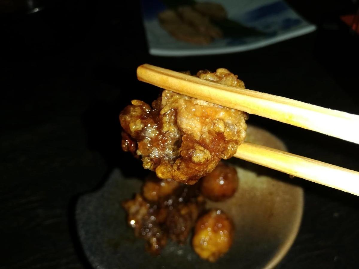 『秋田きりたんぽ屋』の比内地鶏のマタギ揚げを箸で掴んでいる写真