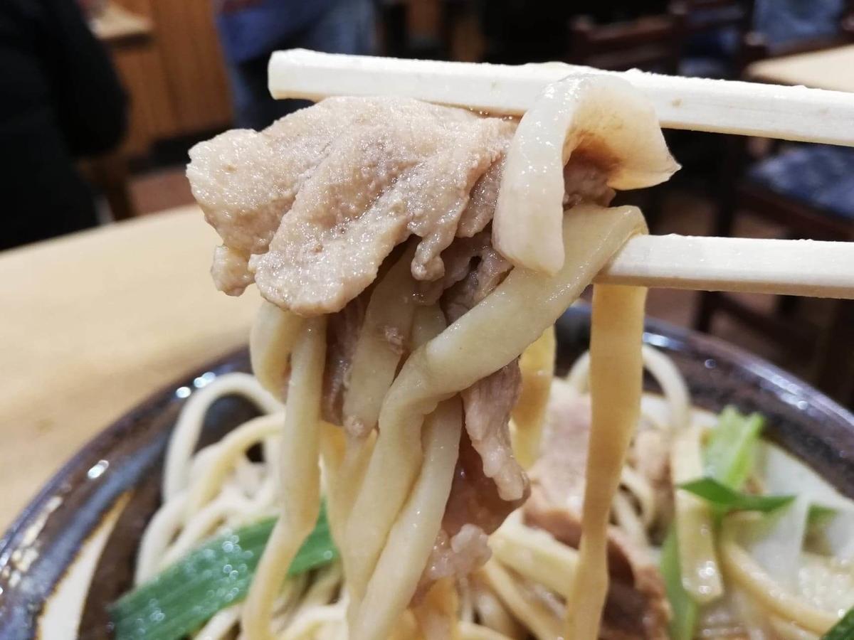 『浅草角萬』の麺と肉南蛮を箸で持ち上げている写真