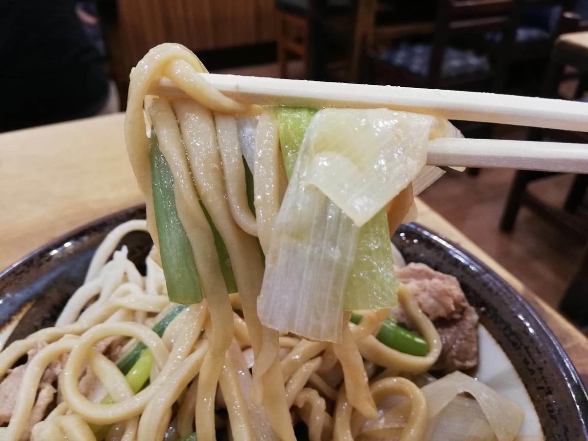 『浅草角萬』の麺とネギを箸で持ち上げている写真