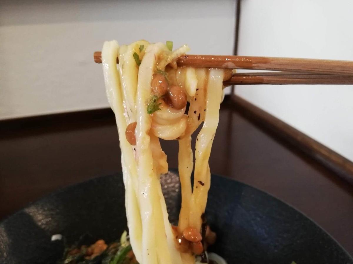 川越『創作うどん専門店くらうど』の、3種のしその納豆おろしうどんの麺を箸で持ち上げている写真