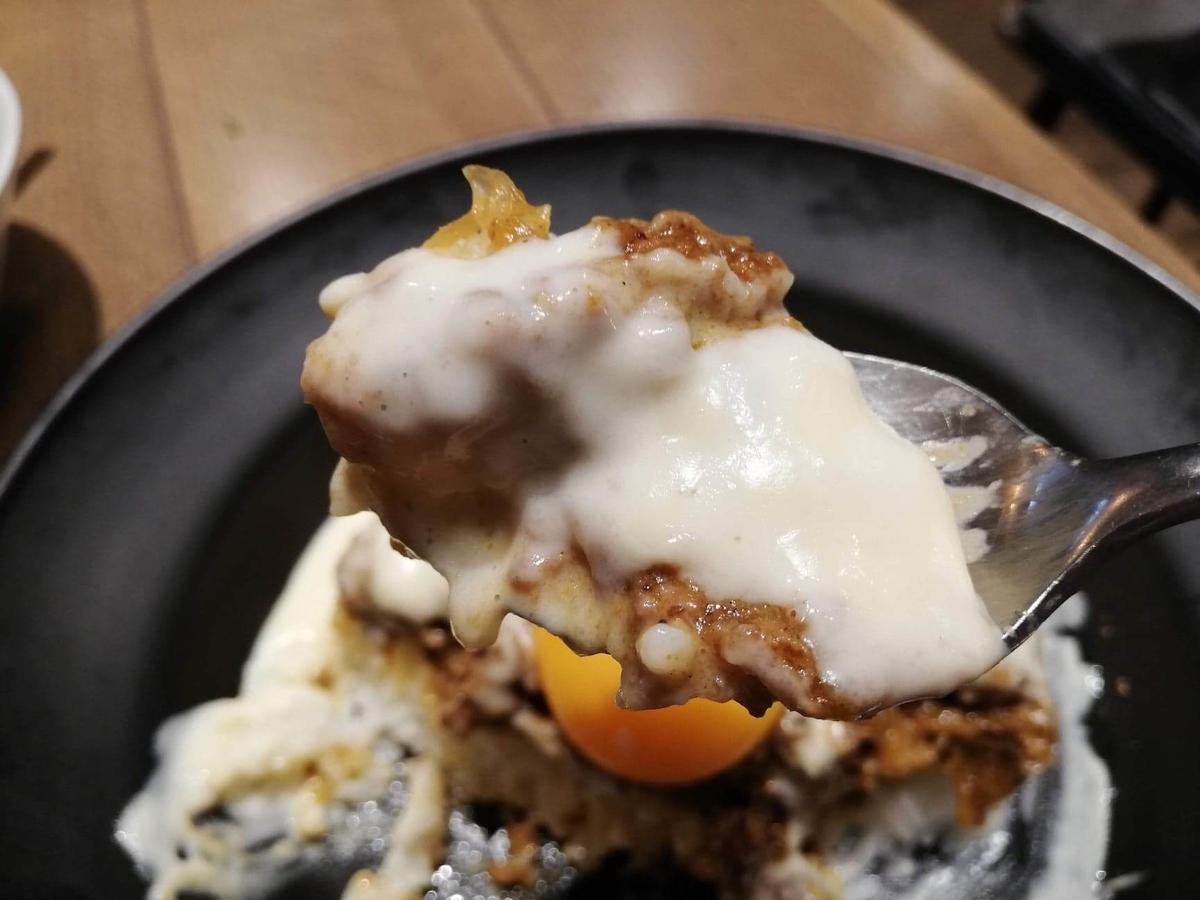 池袋『CHEESE CHEESE & Meat. COMTE』のキーマカレーとチーズをスプーンですくっている写真