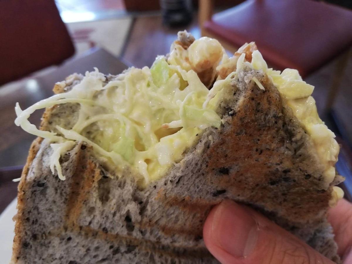 香川県高松市『三びきの子ぶた』の、テリヤキチキンチーズサンドウィッチを持ち上げている写真