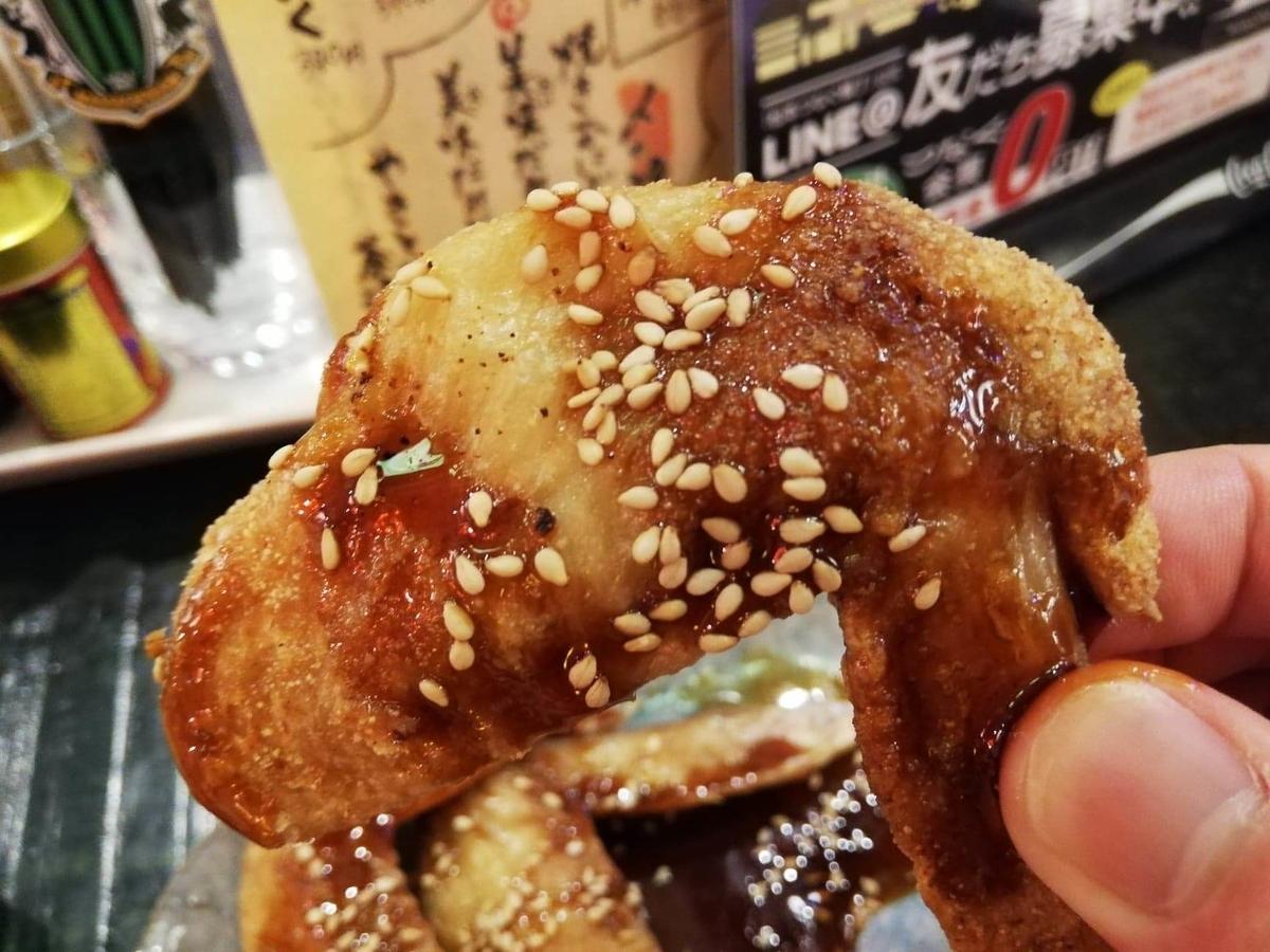 長野県松本市『松本つなぐ横丁』内の『やきとり番長』の手羽先を手で持っている写真