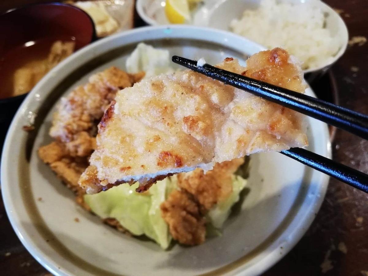長野県松本市中町通り『食い飲み屋 BUN』の山賊焼きを箸で掴んでいる写真