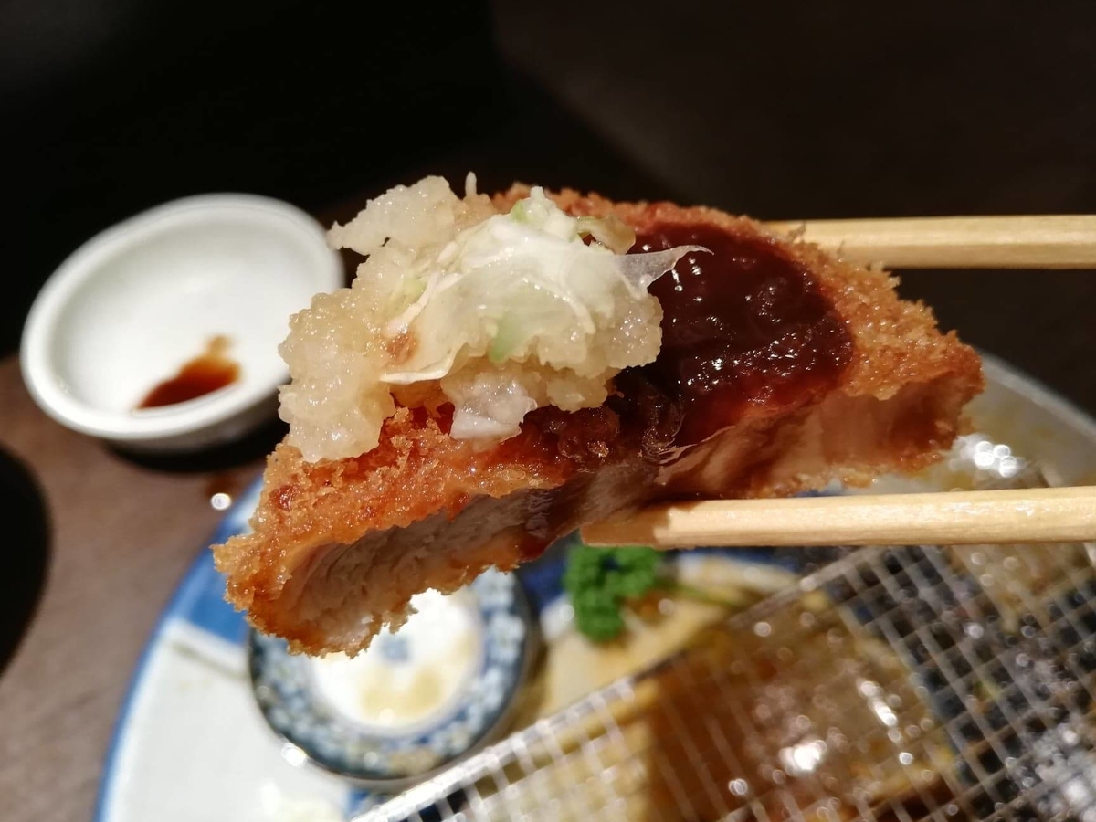 高田馬場『とん久』のとんかつにおろしを乗せて、箸で掴んでいる写真