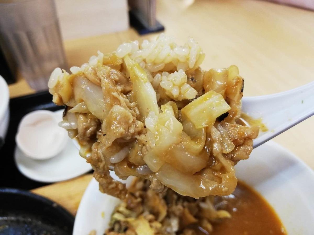 東中野『大盛軒』の鉄板麺をレンゲですくっている写真