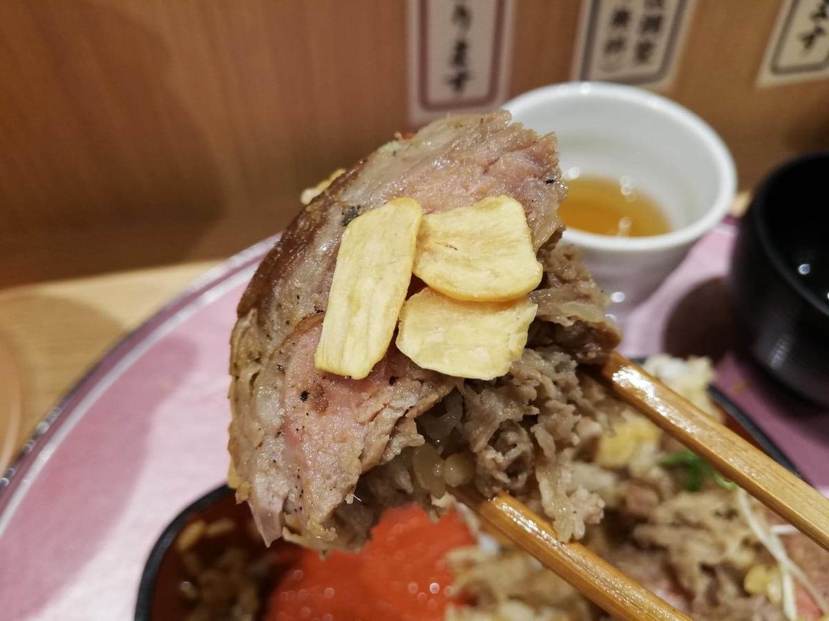 大阪『ビフテキ重・肉飯 ロマン亭』のビフテキにガーリックを乗せた写真