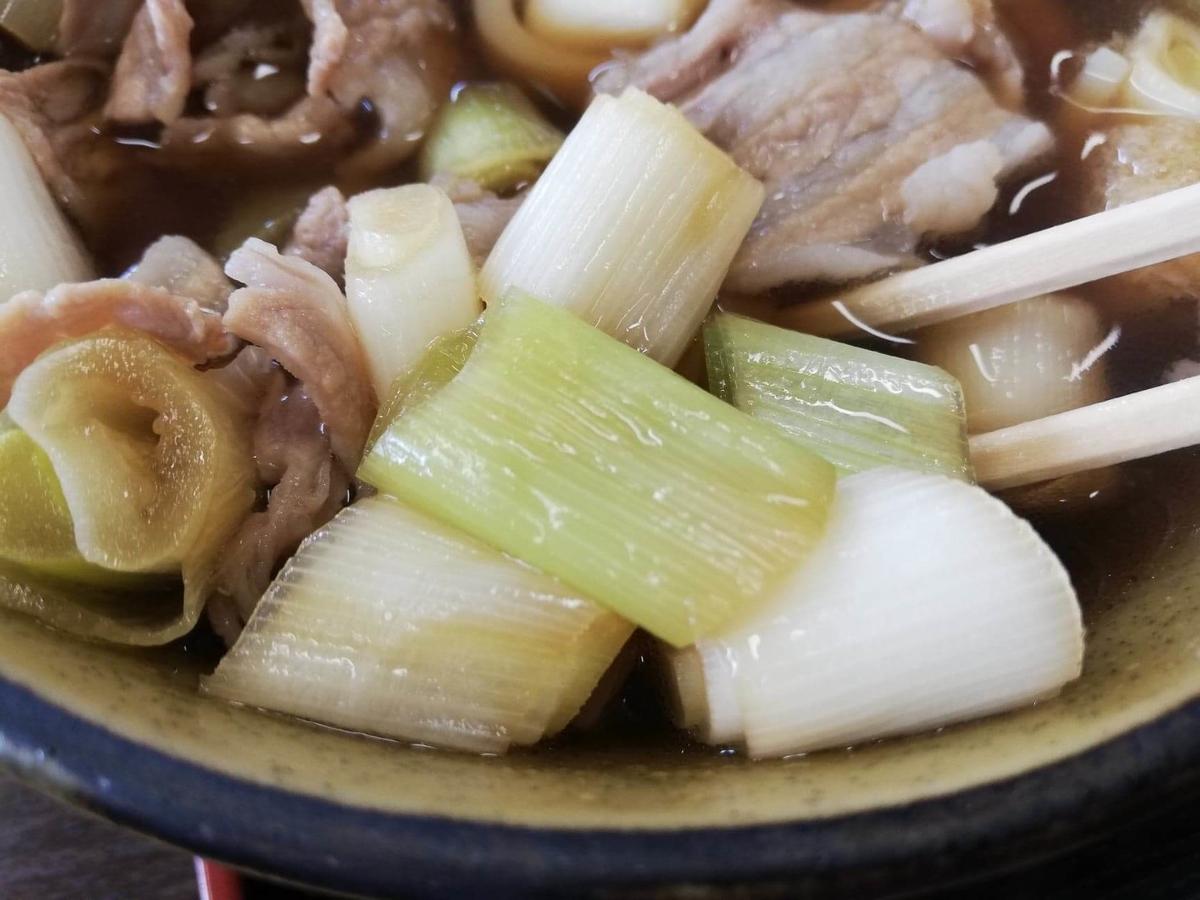 川越『藤店うどん』の肉汁うどんのスープの具材の写真