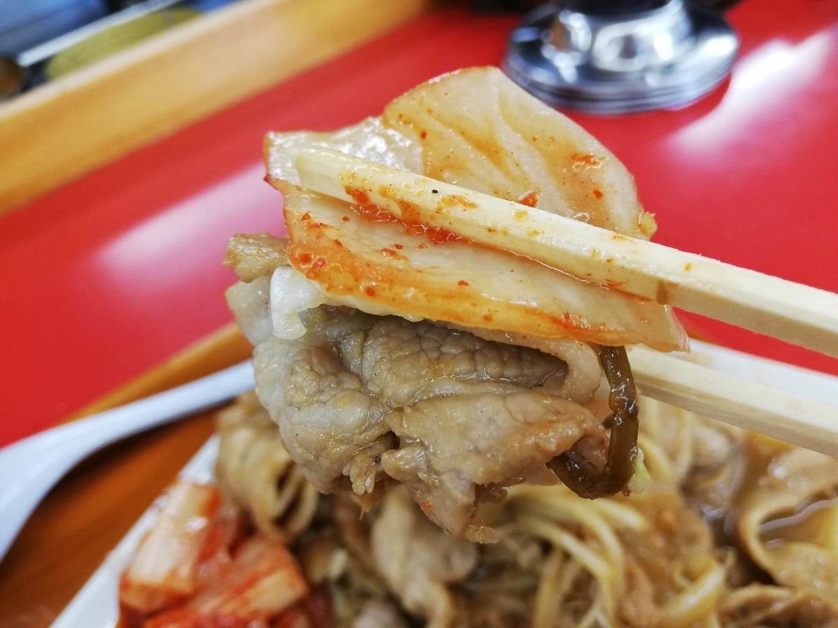 新座『くるまやラーメン』の焼肉とキムチを箸で持ち上げている写真