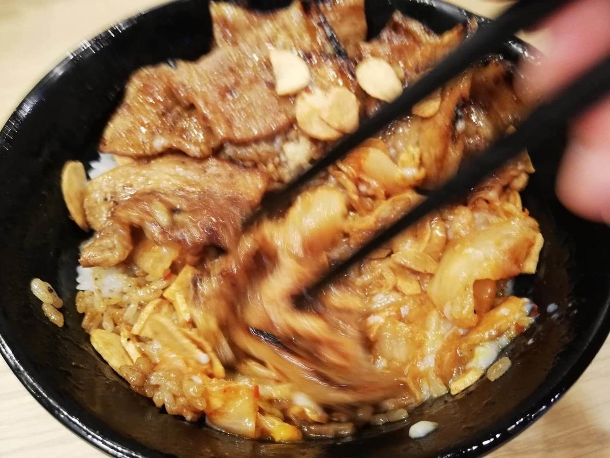 西武新宿『豚大学新宿校舎』の豚丼を箸でかき混ぜている写真