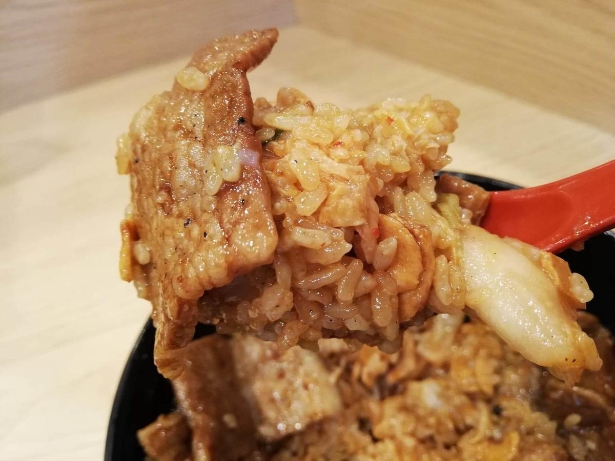 西武新宿『豚大学新宿校舎』の豚丼をレンゲですくっている写真