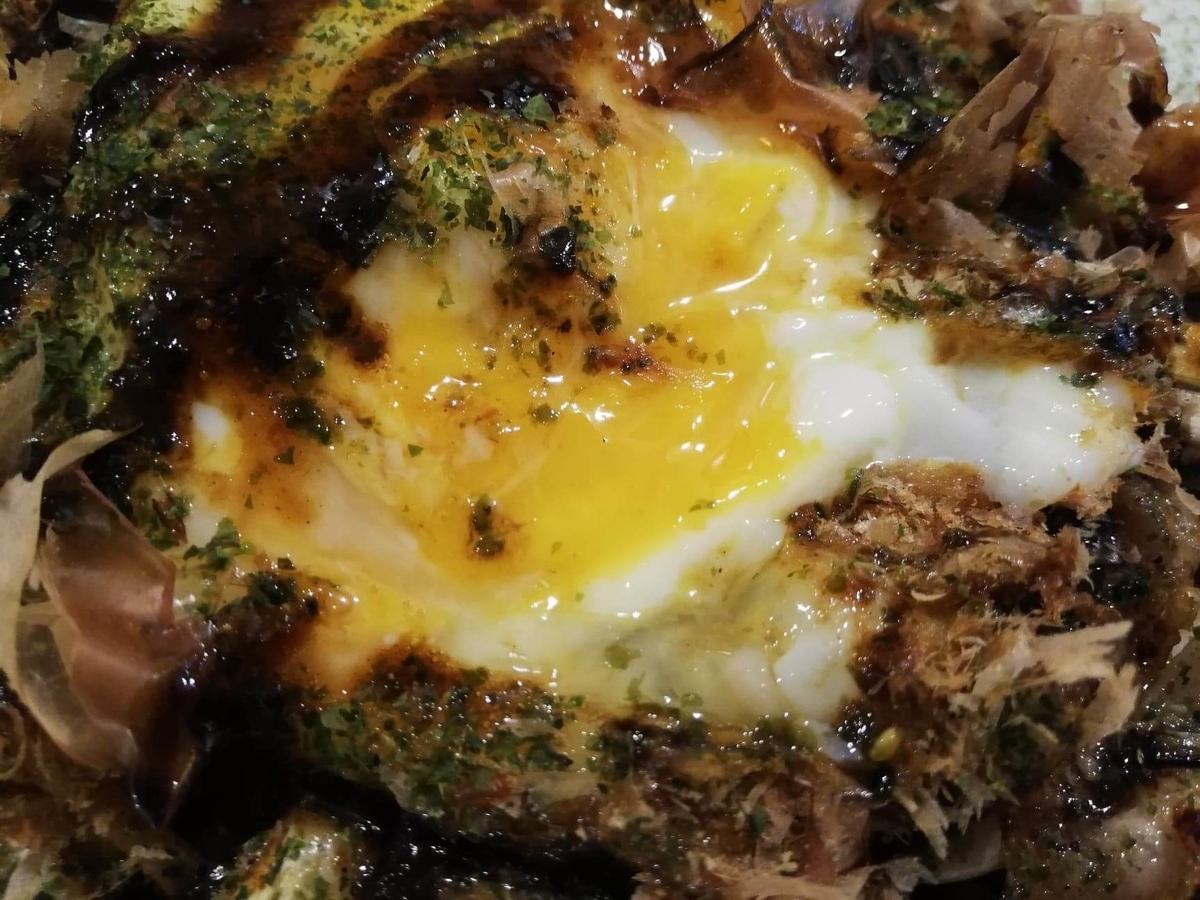 高田馬場『真打みかさ』のソース焼きそばに半熟卵をかけた写真