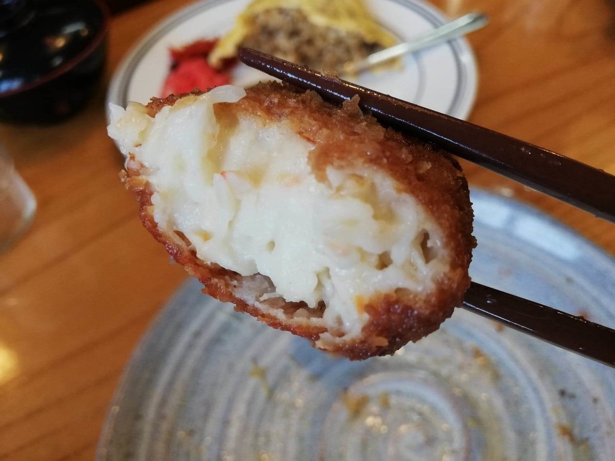 石川県金沢市ひがし茶屋街『自由軒』のクリームコロッケを箸で掴んでいる写真
