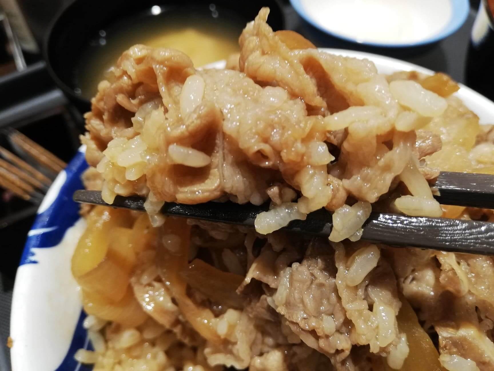 松屋の牛丼を箸で掴んでいる画像