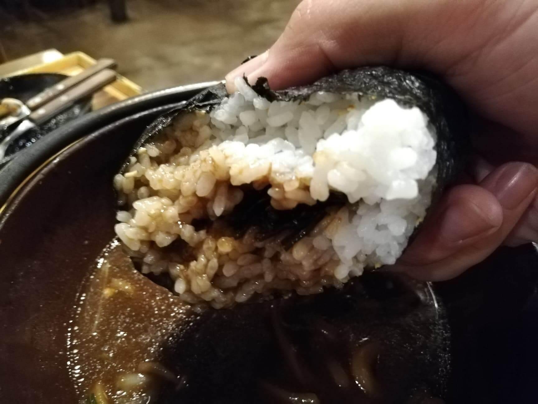 広島県の前空駅『田舎茶屋わたや大野店』の山賊むすびをスープにつけている写真