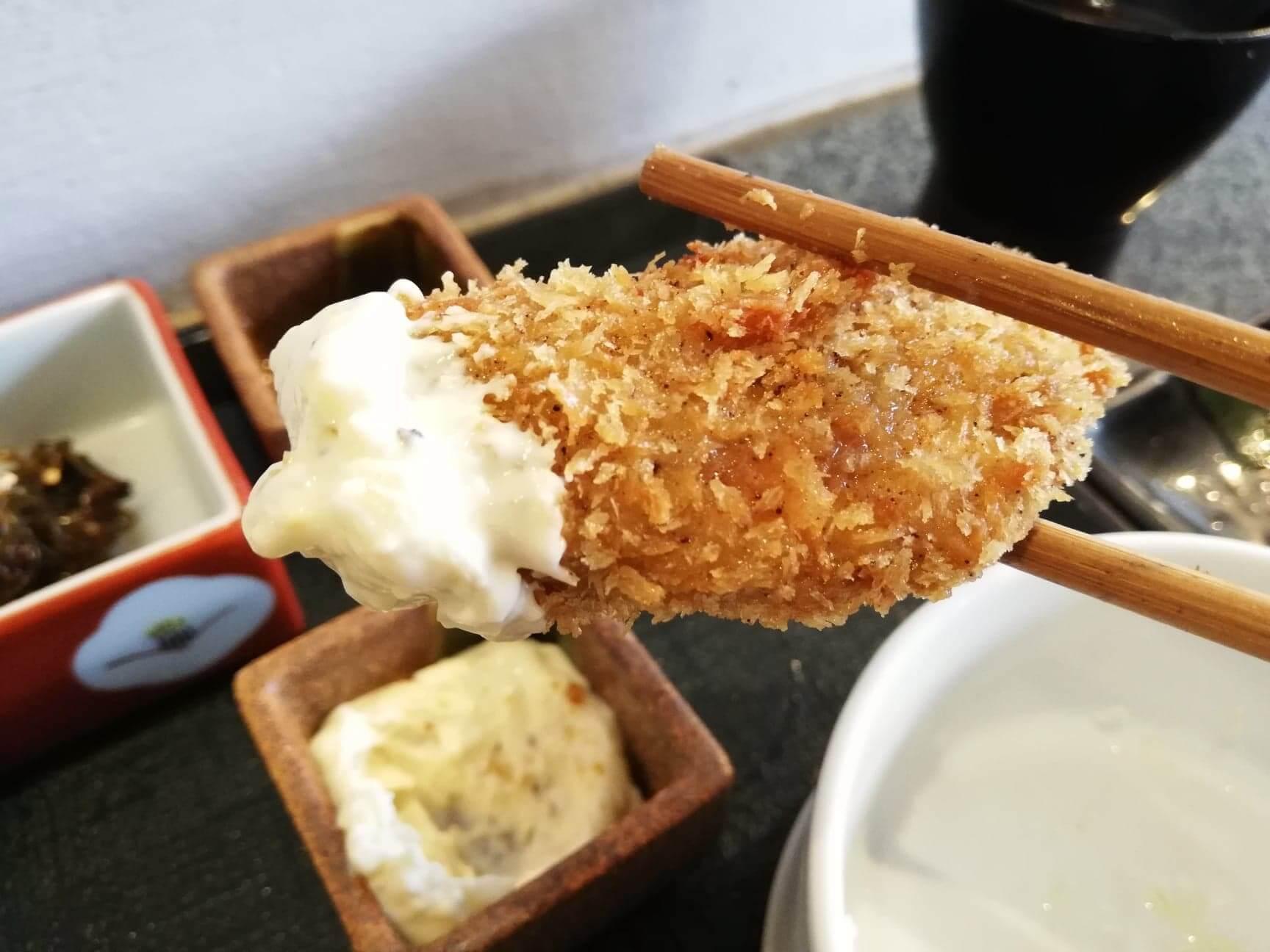 広島県宮島『牡蠣屋』の牡蠣フライにソースをつけている写真