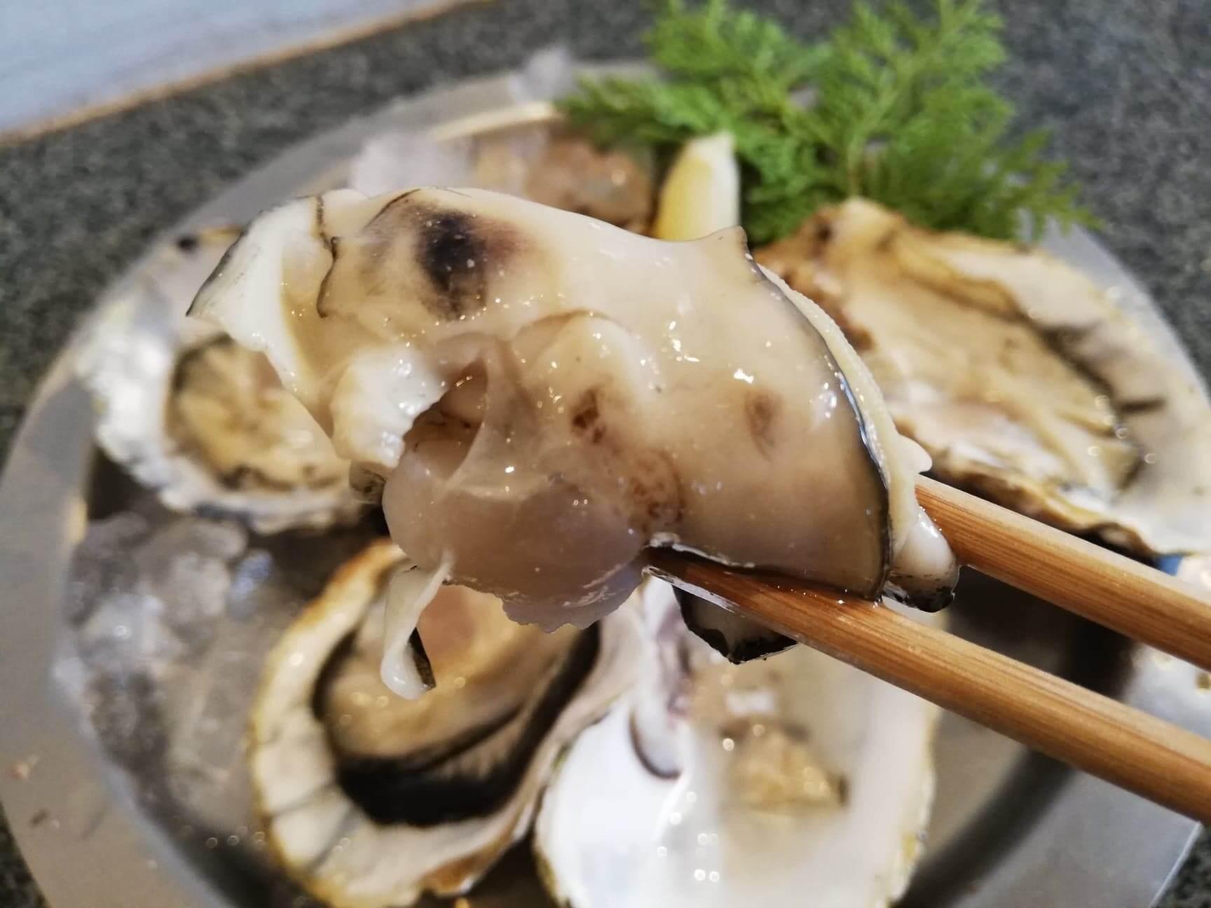 広島県宮島『牡蠣屋』の生牡蠣を箸で掴んだ写真