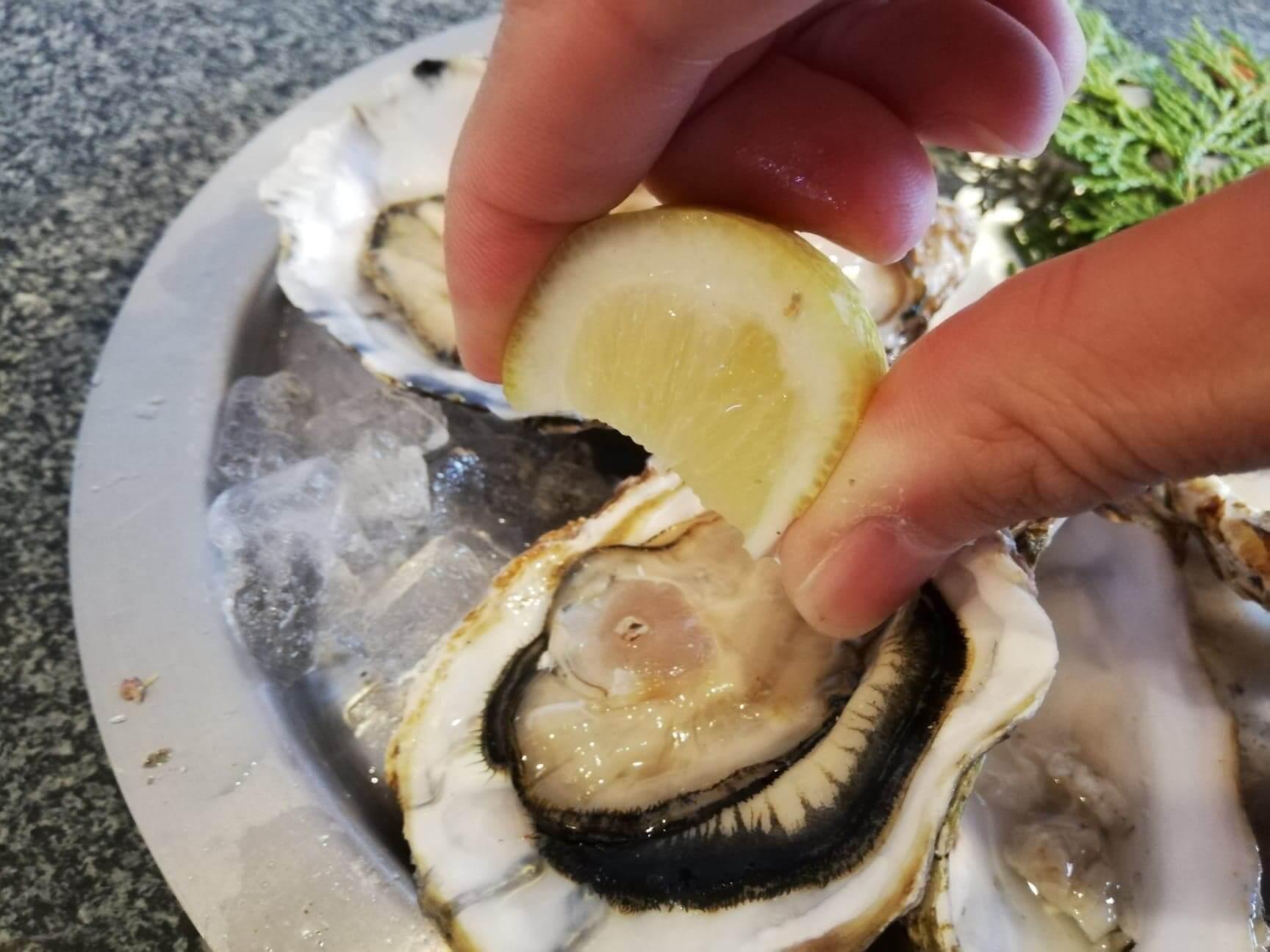 広島県宮島『牡蠣屋』の生牡蠣にレモンをかけている写真