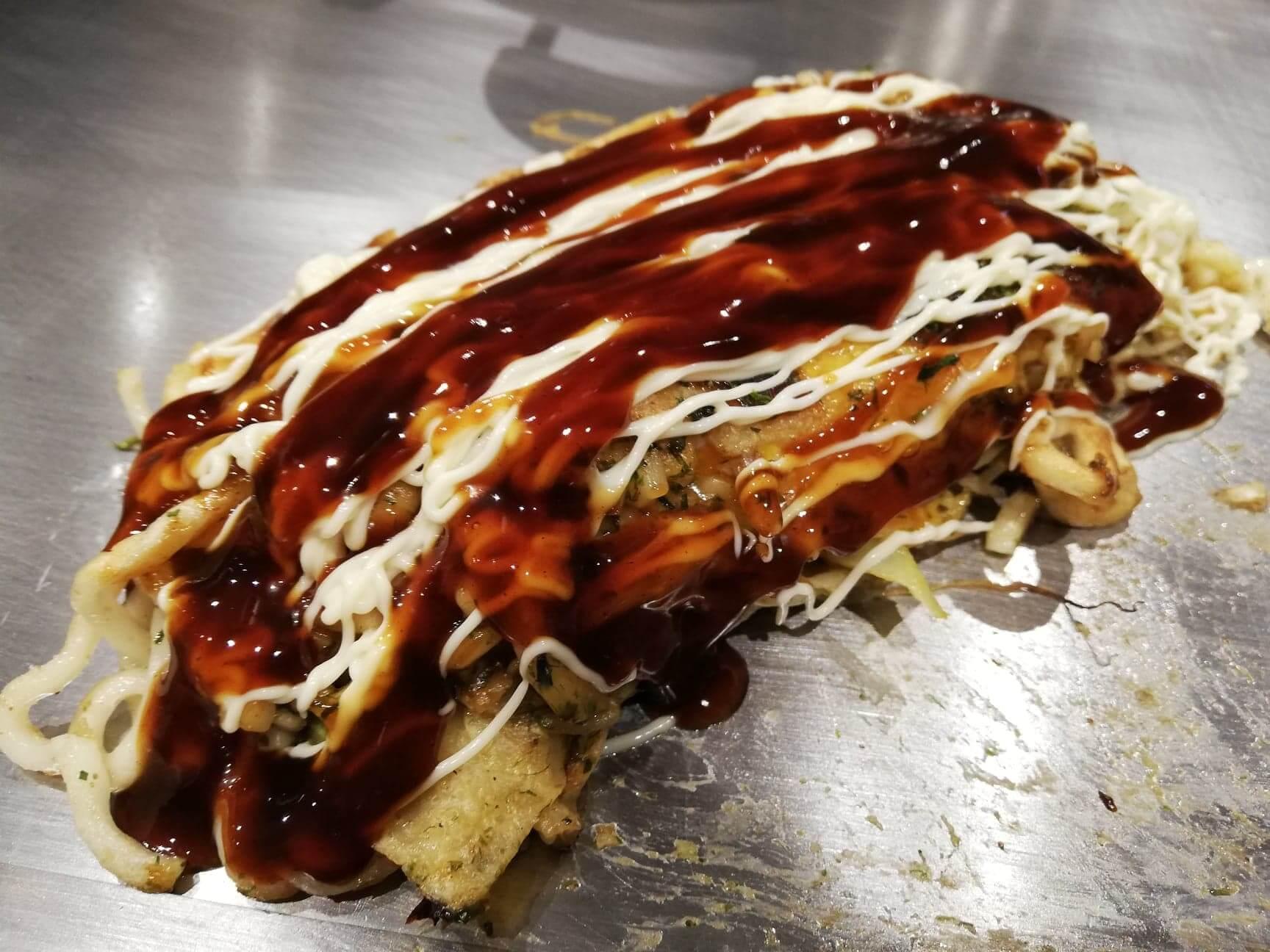 広島県『薬研堀八昌』のうどん肉玉に調味料をかけた写真
