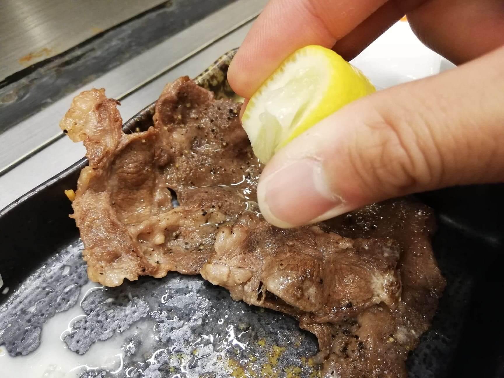 広島『本家村長の店』のタン塩にレモンをかけている写真