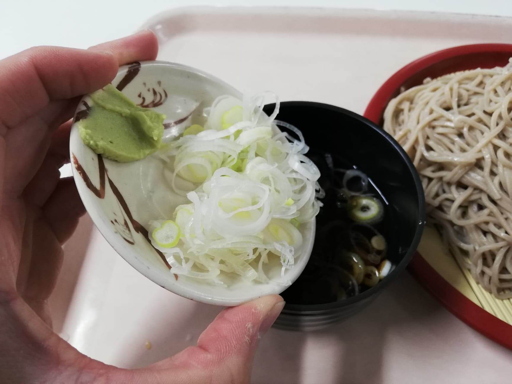 練馬区役所の職員レストランの『富士山もりそば』のめんつゆにネギを入れている写真