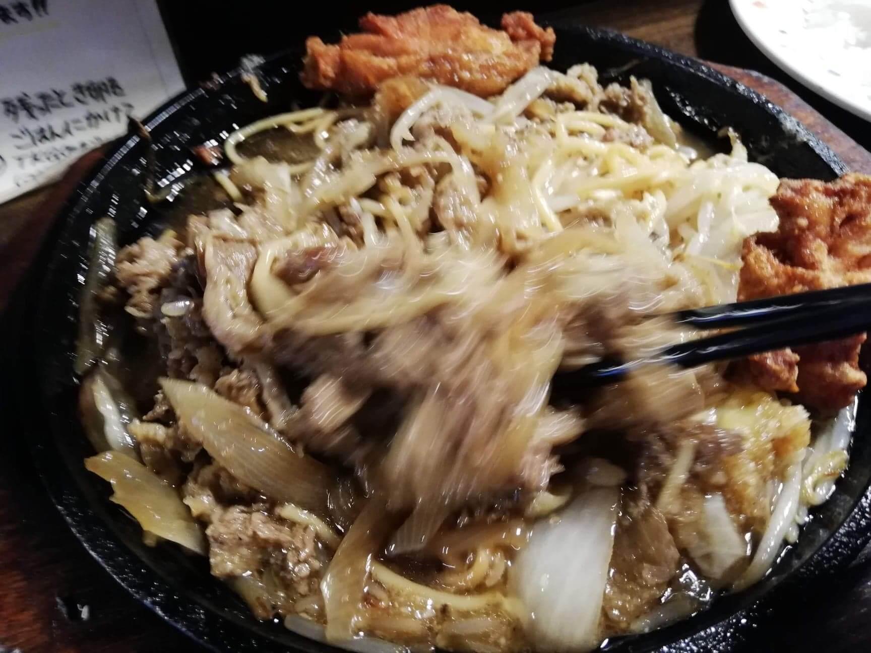 池袋『牛焼ジョニー』のジョニーの牛焼きを箸でかき混ぜている写真
