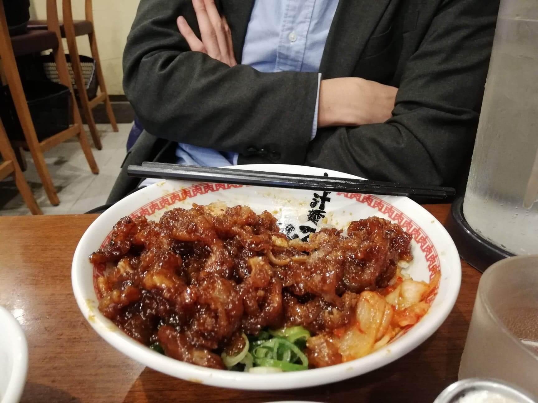 高田馬場『肉汁麺ススム』の肉汁丼の前で腕を組んでいる男性の写真